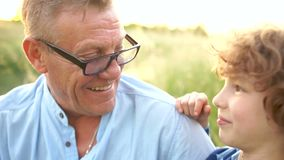 Close-up portrait of grandfather and grandson. Two generations have fun in nature - laughing and fooling around. Happy stock footage
