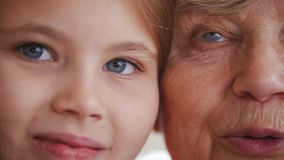 Close up portrait of grandmother and granddaughter. Blue eyes stock footage