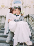The close-up portrait of the groom kissing the bride while carrying. Royalty Free Stock Images