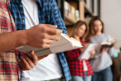 Close up portrait of a group of students holding books. While standing at the bookshelf in library Royalty Free Stock Image