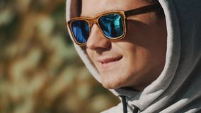 Close up portrait of a guy in hood and sunglasses smiles on summer windy day stock footage