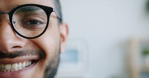 Close-up portrait of half of male face looking at camera smiling indoors stock footage