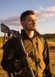 Close up Portrait of hamdsome Hunter. Hunter with shotgun gun on hunt. Hunter aiming rifle in forest. Hunter man. royalty free stock photo