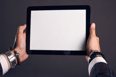 Close-up portrait of hands with tablet. Close-up portrait of hands with a  brutal man holding a tablet on a gray background Royalty Free Stock Photo