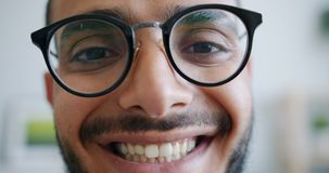Close-up portrait of handsome Arabian man in glasses looking at camera smiling stock video footage
