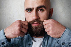 A close-up portrait of handsome balded man having  thick black eyebrows, beard and moustasche, dark eyes wearing casual jean shirt. Holding his hands on Stock Photos