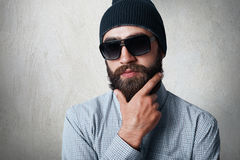 Close-up portrait of handsome bearded man wearing stylish black cap, checked shirt and sunglasses holding his hand on thick beard. Posing against white wall royalty free stock images