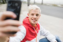 Close up portrait of handsome blond smiling man wlaking in the p royalty free stock photography