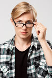 Close up portrait of handsome blond young man wearing casual plaid shirt looking in camera over glasses isolated on grey Royalty Free Stock Photography