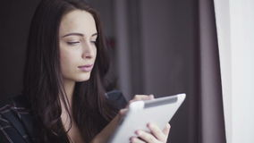 Close-up portrait of a handsome caucasian female in her 20s using tablet indoors. stock footage