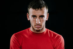 Close up portrait of handsome Caucasian sportsman wearing red sportswear and posing after exercises on dark background. Healthy in. Caucasian sportsman wearing Stock Photo