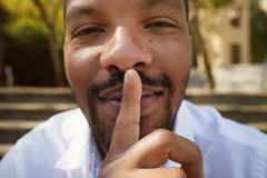 Close up portrait of handsome cheerful mysterious silent american african man making hush gesture royalty free stock photo