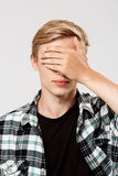 Close up portrait of handsome confident blond young man wearing casual plaid shirt covering eyes with hand, isolated on Stock Image