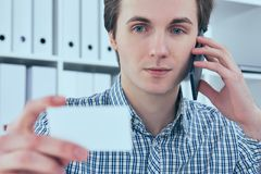 Close-up portrait of handsome european businessman talking on the phone and holding business card at workplace. Close-up portrait of handsome european Stock Image