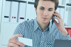 Close-up portrait of handsome european businessman talking on the phone and holding business card at workplace. Close-up portrait of handsome european Royalty Free Stock Photography