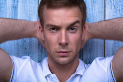 Close up portrait of a handsome fashion model posing male. Close up portrait of a handsome male fashion model posing with hands behind head Royalty Free Stock Photos