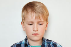A close-up portrait of handsome little boy with fair hair and blue eyes dressed in checked shirt having sad expression looking dow Stock Images