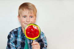Close up portrait of handsome male child with blond hair and blue eyes dressed in checked shirt holding huge sweet candy in his ha. Nd looking with surprise at Royalty Free Stock Photos
