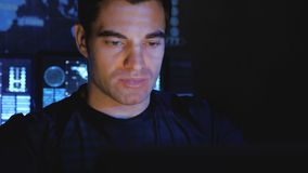 Handsome male hacker programmer works at a computer at night in a data center filled with monitor screens. Close-up portrait of Handsome male hacker programmer stock video footage