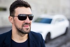 Close up portrait of handsome man in sunglasses with his car royalty free stock photo