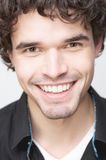 Close Up Portrait of a Handsome Man with Toothy Smile. Close up portrait of a handsome young man with a smiling expression on his face. He is wearing a black Stock Photos