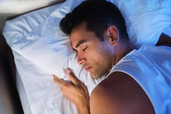 Close-up portrait of handsome man on the white bed. View from ab. Ove Stock Images