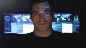 Close up portrait of handsome programmer geek in a data center filled with monitor screens