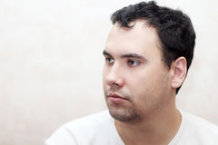 Close up portrait of handsome serious man in white t-shirt Stock Photos