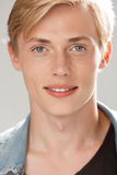 Close up portrait of handsome smiling blond young man wearing casual black t-shirt and jeans jacket looking in camera on Stock Photo