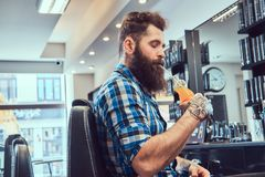 Handsome bearded man in the barbershop. Close-up portrait of a handsome stylish bearded male with a tattoo on arm dressed in a flannel shirt drinks juice in a stock photo