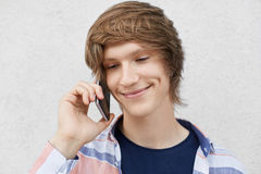 Close up portrait of handsome teenage boy with trendy hairstyle, smiling gently having dimples on cheeks, calling his best friend Stock Photography