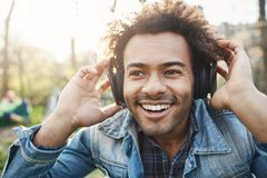 Close-up portrait of handsome unshaved dark-skinned guy holding hands on headphones while listening music and being. Excited, looking aside, sitting in park Royalty Free Stock Image