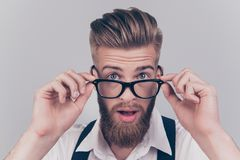 Close up portrait of handsome virile masculine emotion expressin. G groomed classy smart intelligent clever manager with big eyes touching rimmed glasses Royalty Free Stock Photography