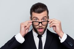 Close up portrait of handsome wondered attractive shocked amazed. With big eyes mouth modern trendy stylish hairdo hairstyle taking-off glasses white shirt tie Stock Image