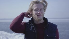 Close-up portrait of handsome young blond man in glasses looking away touching his hair. Attractive guy of Scandinavian stock video