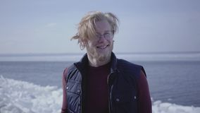 Close-up portrait of attractive young blond man in glasses looking away touching his hair. Attractive guy of. Close-up portrait of a handsome young blond man in stock video