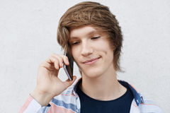 Close up portrait of handsome young boy with narrow dark eyes, stylish hairdo, dimple on cheek holding his mobile phone on ear cal royalty free stock photos