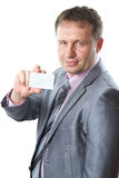 Close up portrait of a handsome young business man in a stylish suit holding blank business card, copy space, isolated Royalty Free Stock Photos