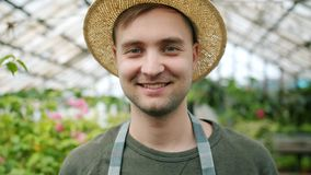 Close-up portrait of handsome young gardener in hat and apron in greenhouse. Smiling looking at camera. Happiness, people and lifestyle concept stock video