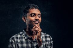 Portrait of a handsome young Indian guy wearing a checkered shirt holding hand on chin and looking at a camera with a stock photo