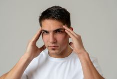 Young attractive man in pain with headache suffering migraines stock photography