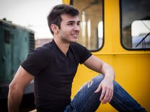 Close-up portrait of handsome young man outside. On old yellow train, looking away Stock Photography