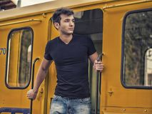 Close-up portrait of handsome young man outside. On old yellow train, looking away Stock Photo
