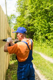 Close up portrait of handy carpenter fixes wooden fence Stock Photography