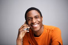 Close up happy african american man talking on cellphone against gray background. Close up portrait of happy african american man talking on cellphone against royalty free stock images