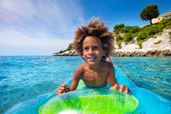 African boy swimming on air mattress in the sea. Close-up portrait of happy African boy swimming on big air mattress in the sea royalty free stock photo
