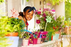 Happy African girl watering flowers on the balcony stock image