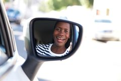 Close up happy african woman driving car and looking in side mirror royalty free stock photo
