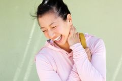 Close up happy asian woman laughing against green wall Stock Images