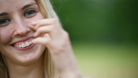 Close-up portrait of a happy attractive Caucasian blonde girl with wet hair during a rain on the nature outdoor on a stock video footage